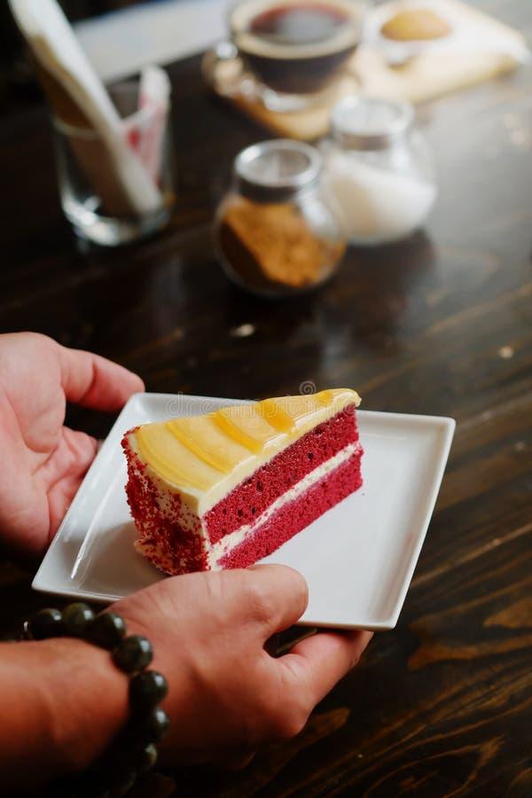 A servi un morceau de gâteau rouge de velours avec la main pour deux hommes avec le fond dinning en bois de table images stock