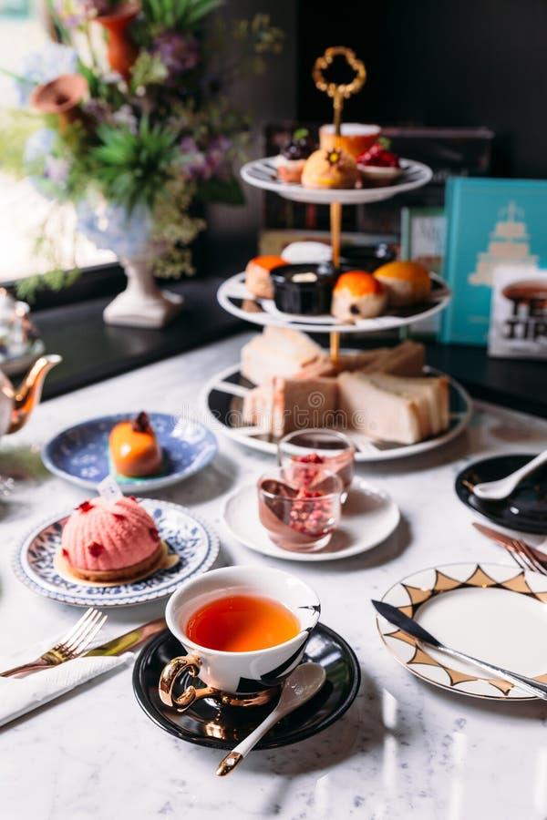 Service à thé anglais d'après-midi comprenant le thé chaud, la pâtisserie, les scones, les sandwichs et les mini tartes sur la ta photos stock
