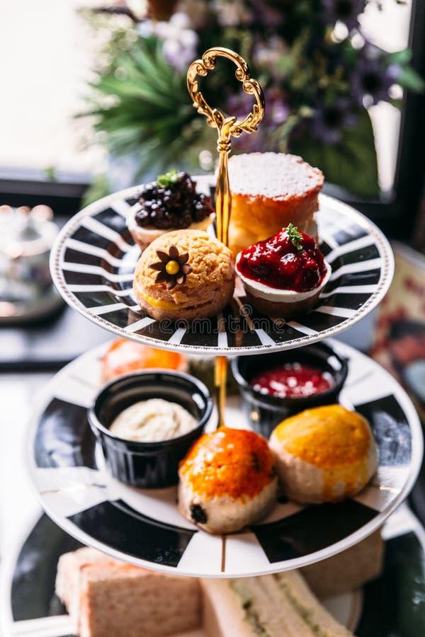 Service à thé anglais d'après-midi comprenant le thé chaud, la pâtisserie, les scones, les sandwichs et les mini tartes sur la ta photo stock