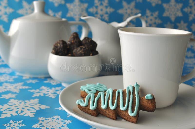 Service à thé blanc avec des bonbons à biscuit de miel de Noël et à noix et à date de chocolat sur le fond bleu d'hiver avec des  photo libre de droits