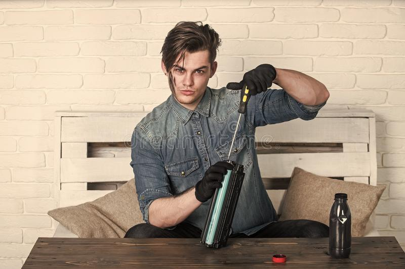 Service center and workshop concept. Man refilling cartridge toner for printer. Ink bottle on wooden table. Student with dirty face in blue jean shirt royalty free stock photo