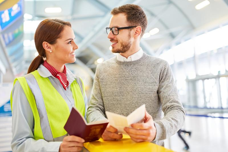 Service clerk and passenger with travel documents. At the airport check-in counter stock photography