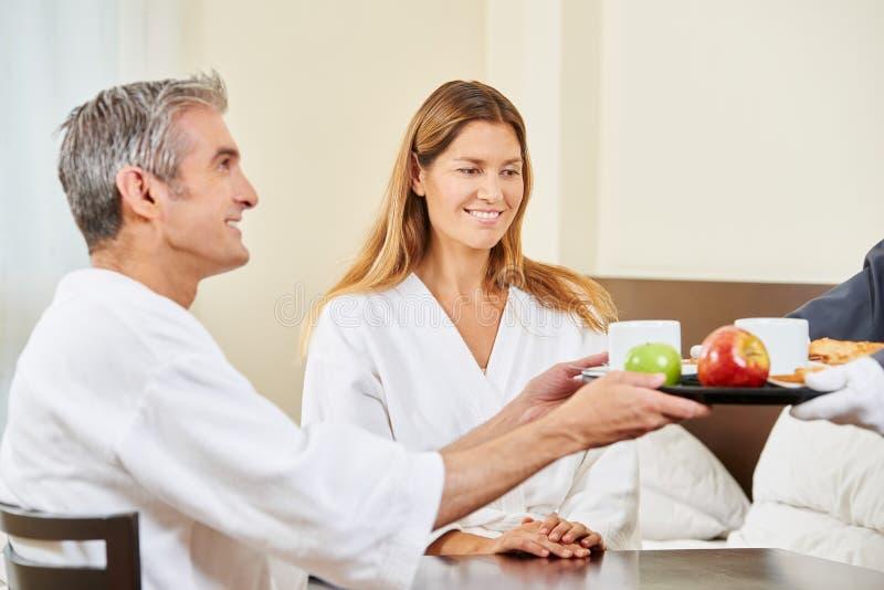 Service d'étage apportant le petit déjeuner dans le lit pour des couples photo libre de droits