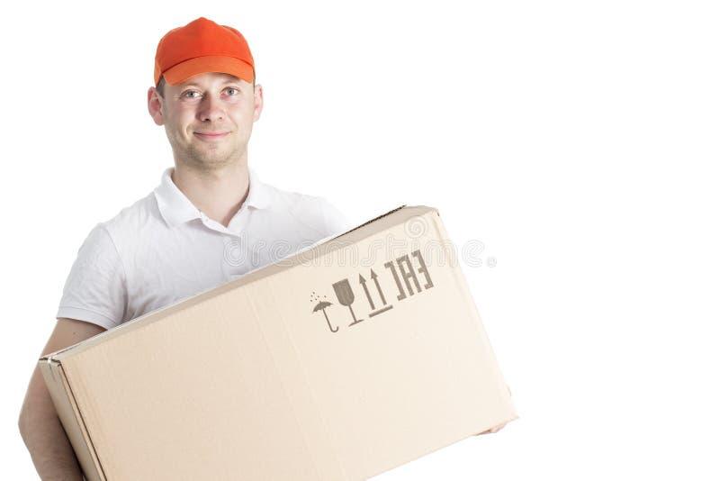 Service de distribution de travailleur de messager dans le chapeau avec la boîte en carton dans des mains d'isolement sur le fond photo stock
