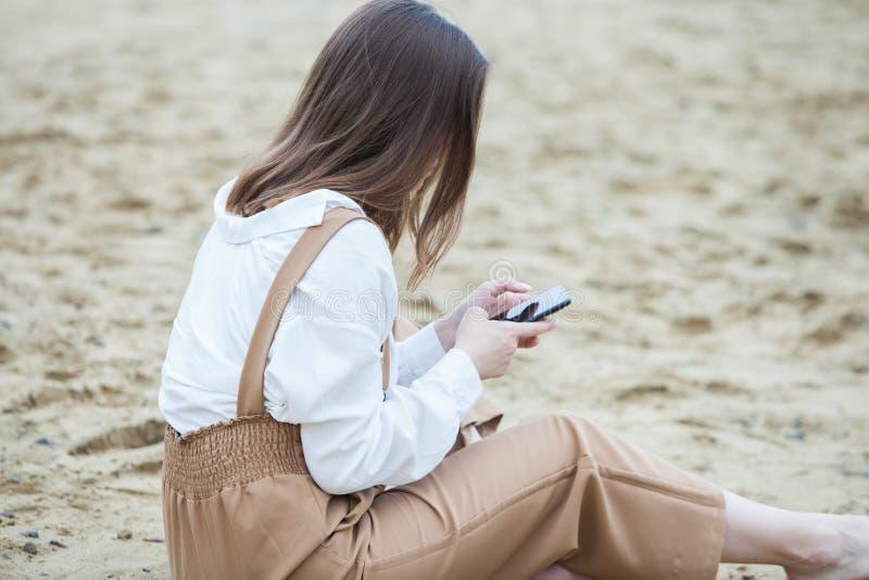 Service de mini-messages d'extérieur de fille à son téléphone portable Fille avec le t?l?phone Portrait d'un message heureux de s photographie stock libre de droits