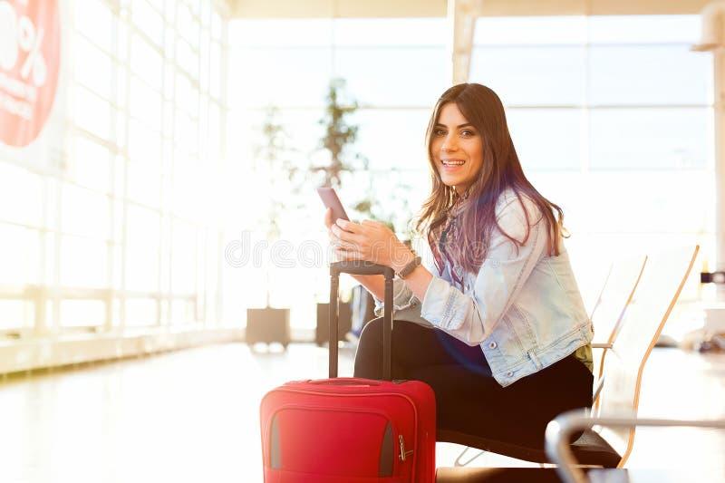Service de mini-messages de femme et téléphone d'utilisation avant de monter dans l'avion photographie stock libre de droits