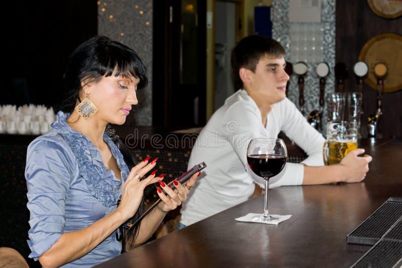 Service de mini-messages de femme sur son mobile à la barre photo stock