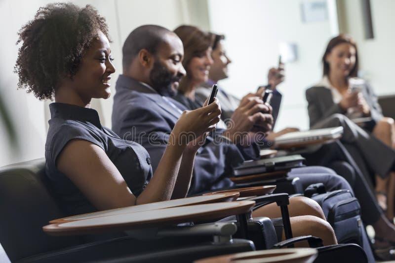 Service de mini-messages de fille de femme d'afro-américain sur l'aéroport de téléphone portable photographie stock libre de droits