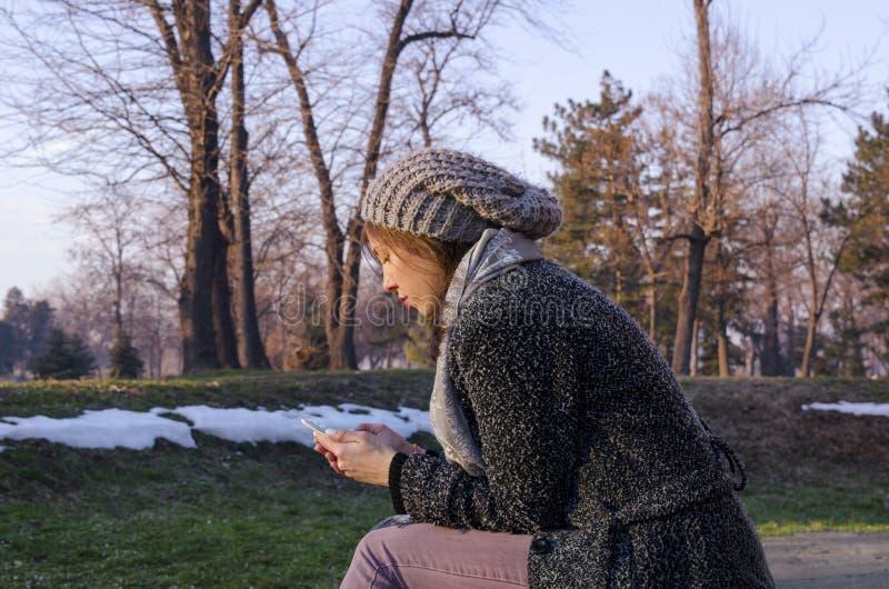 Service de mini-messages de jeune femme en hiver images stock
