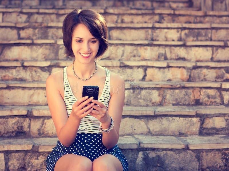 Service de mini-messages de sourire de fille de hippie avec son téléphone portable image libre de droits