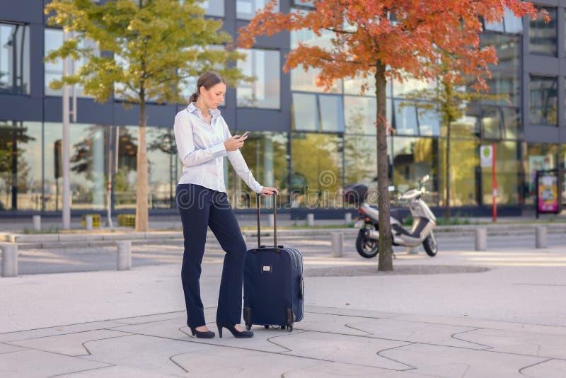 Service de mini-messages de voyageuse de jeune femme à un téléphone portable photographie stock