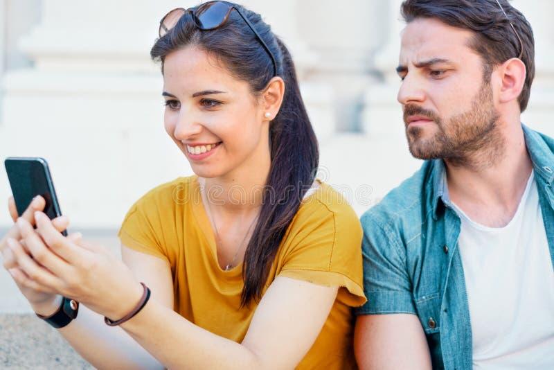 Service de mini-messages fâché d'homme et de femme au téléphone image stock