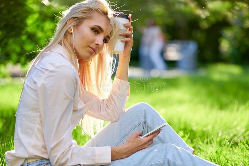 Service de mini-messages femelle de jeunes heureux attrayants ? son t?l?phone portable en dehors de la pose dans l'herbe photos libres de droits