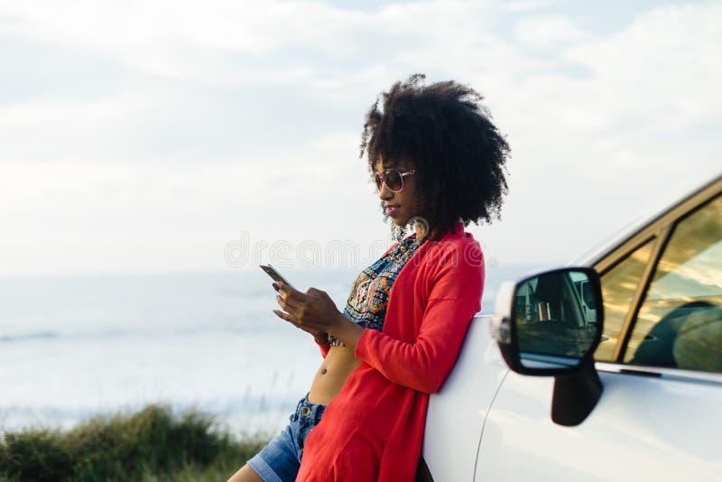 Service de mini-messages de femme à son téléphone pendant le voyage de voiture à la côte photo stock