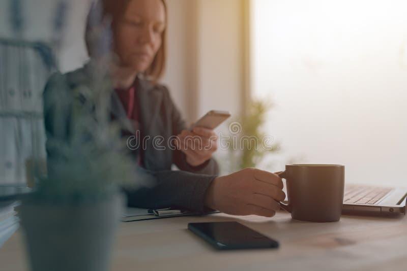 Service de mini-messages de femme d'affaires au téléphone portable pendant la pause-café du bureau images libres de droits