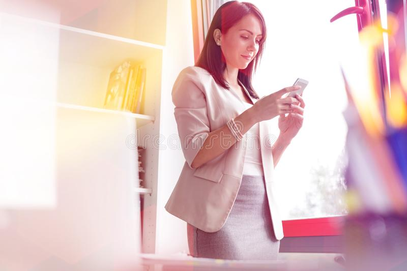 Service de mini-messages de femme d'affaires sur le smartphone par la fen?tre au bureau image stock