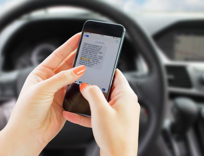 Service de mini-messages de femme tout en conduisant sa voiture photo stock