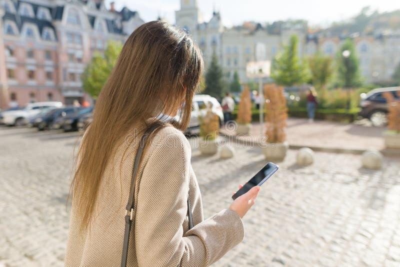 Service de mini-messages de jeune femme au téléphone intelligent marchant dans la rue ensoleillée de ville, fille portant le mant images libres de droits