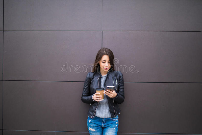 Service de mini-messages de jeune femme et café joyeux de participation tout en se penchant contre le mur dans l'extérieur urbain images libres de droits