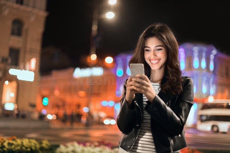 Service de mini-messages de jeune fille au téléphone, marchant dans la ville la nuit images stock