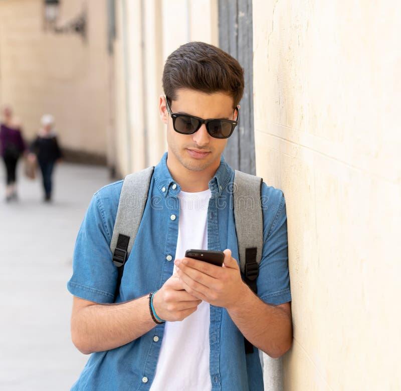 Service de mini-messages masculin de jeune étudiant heureux à son téléphone intelligent dans ci moderne image stock