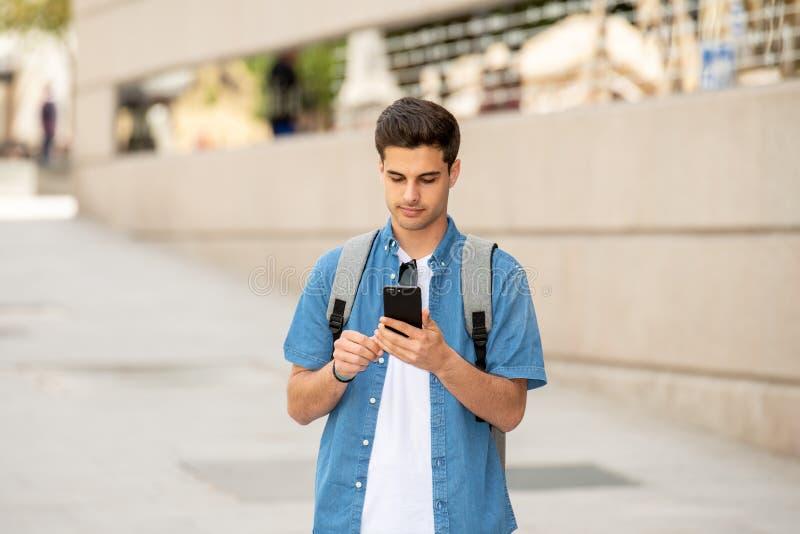 Service de mini-messages masculin de jeune étudiant heureux à son téléphone intelligent dans la ville moderne photographie stock libre de droits