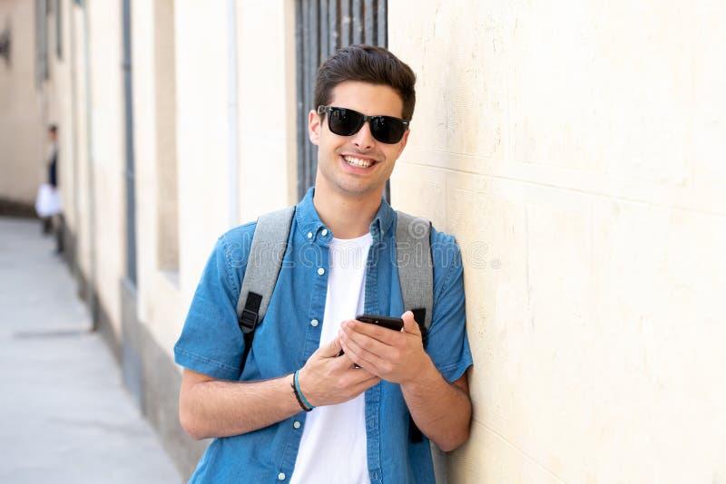 Service de mini-messages masculin de jeune étudiant heureux à son téléphone intelligent dans la ville moderne images libres de droits