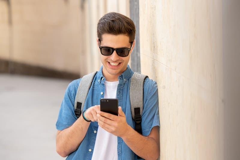 Service de mini-messages masculin de jeune étudiant heureux à son téléphone intelligent dans la ville moderne images stock