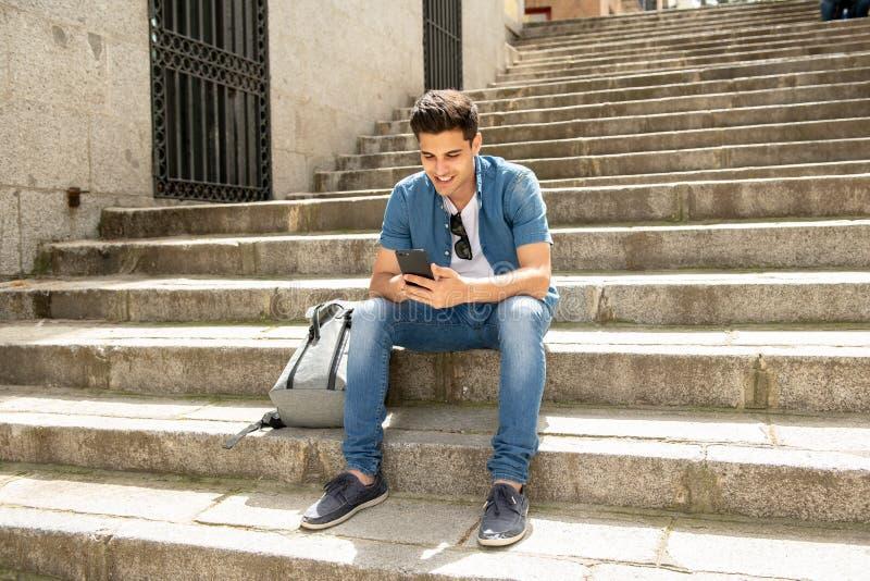 Service de mini-messages masculin de jeune étudiant heureux à son téléphone intelligent dans la ville moderne photo stock