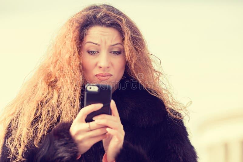 Service de mini-messages parlant de femme malheureuse sceptique bouleversée au téléphone portable image libre de droits
