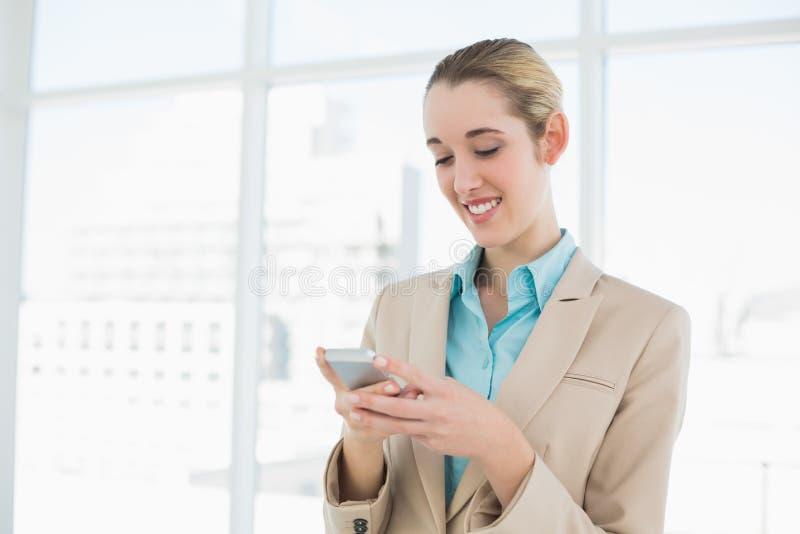 Service de mini-messages ponytailed attrayant de femme d'affaires avec son smartphone photo stock