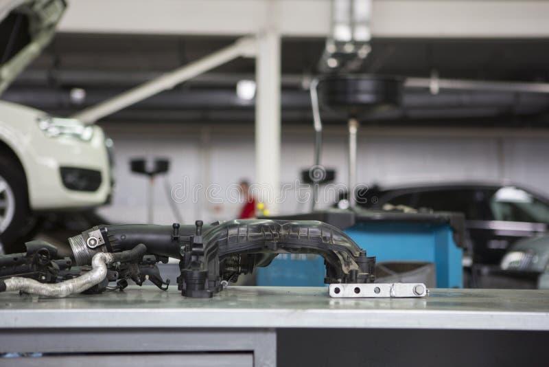 Service de voiture dans les pièces de moteur de premier plan sur la table, sur les voitures troubles d'un fond sur les remonte-pe photographie stock libre de droits