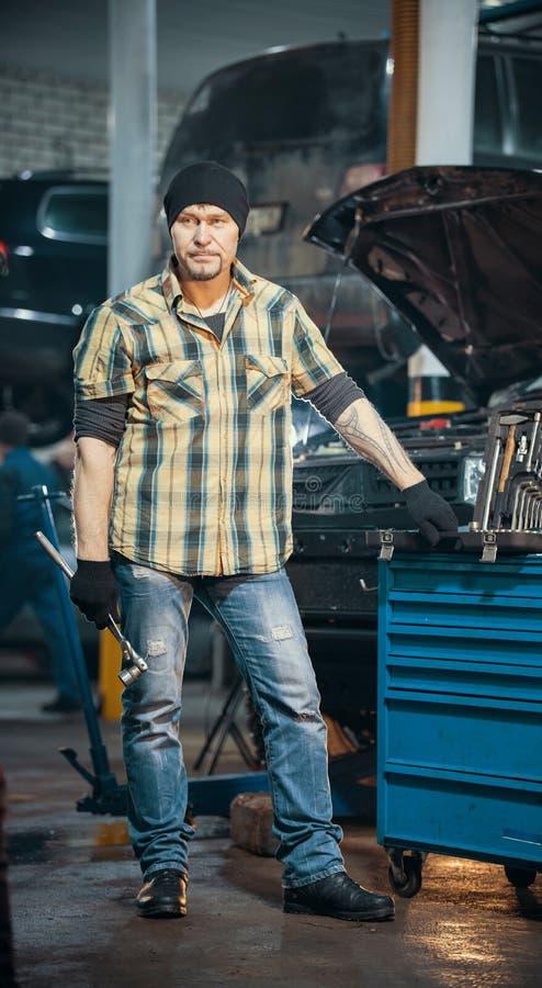 Service des réparations de voiture L'homme sérieux brutal de mécanicien se tient à côté de la valise d'outillage et de tenir une  photographie stock