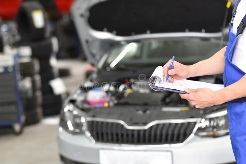 Service et inspection d'une voiture dans un atelier - le mécanicien inspectent images stock