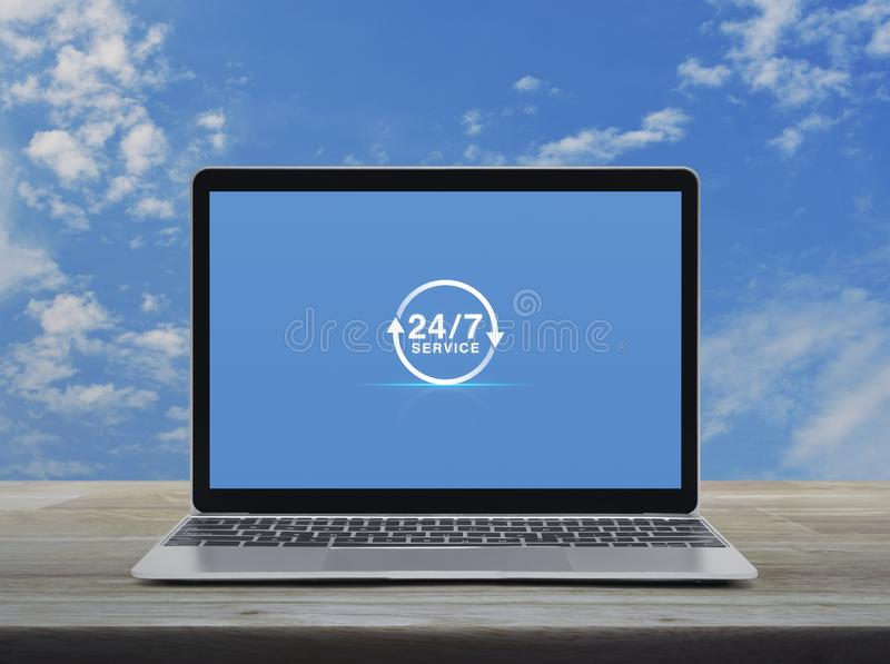 Business full time service online concept. 247 service icon with modern laptop computer on wooden table over blue sky with white clouds, Business full time royalty free stock image