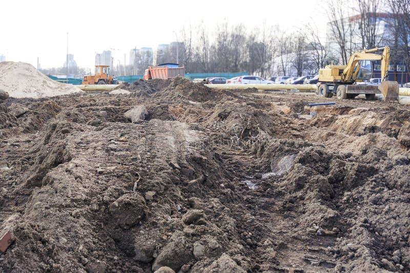 Service industriel creusé plus de chantier de construction, danger il y a un tracteur avec un seau photographie stock libre de droits