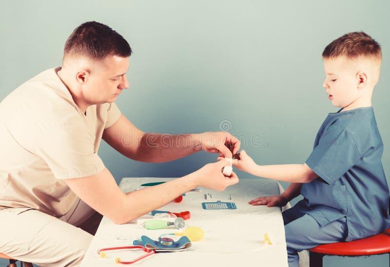 Service médical Homme-médecin assis table des outils médicaux pour examiner un petit garçon Concept de pédiatre Soins de santé photo stock