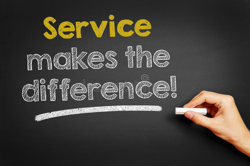 Service makes the difference!. Hand writes Service makes the difference! on blackboard stock photos
