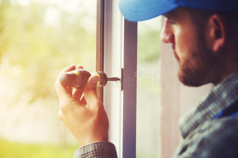 Service man installing window stock photography