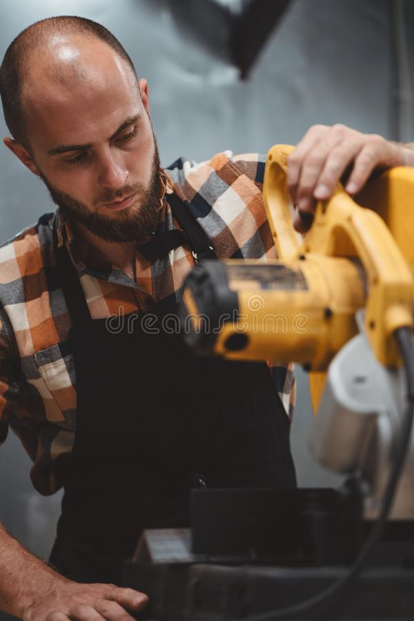 Service mechanic working on electrical grinding machine in service station. Servicing of machines. Workflow at the factory stock image