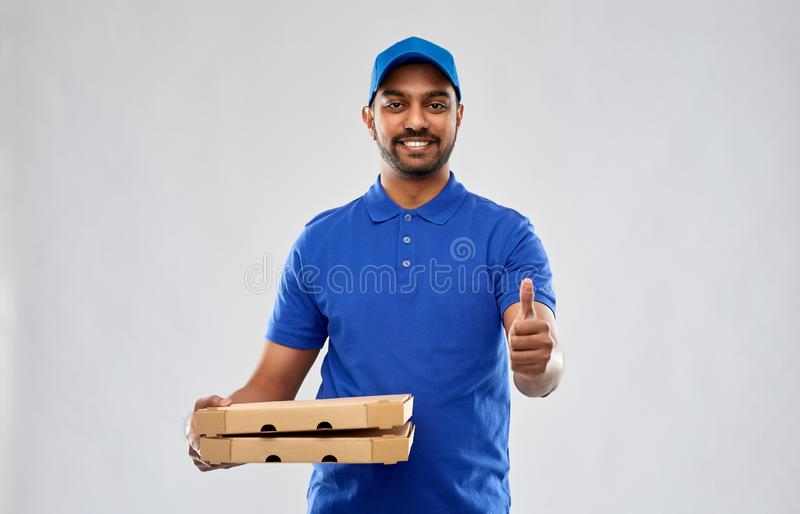 Indian delivery man with pizza showing thumbs up. Service and people concept - happy indian delivery man with pizza boxes in blue uniform showing thumbs up over royalty free stock images