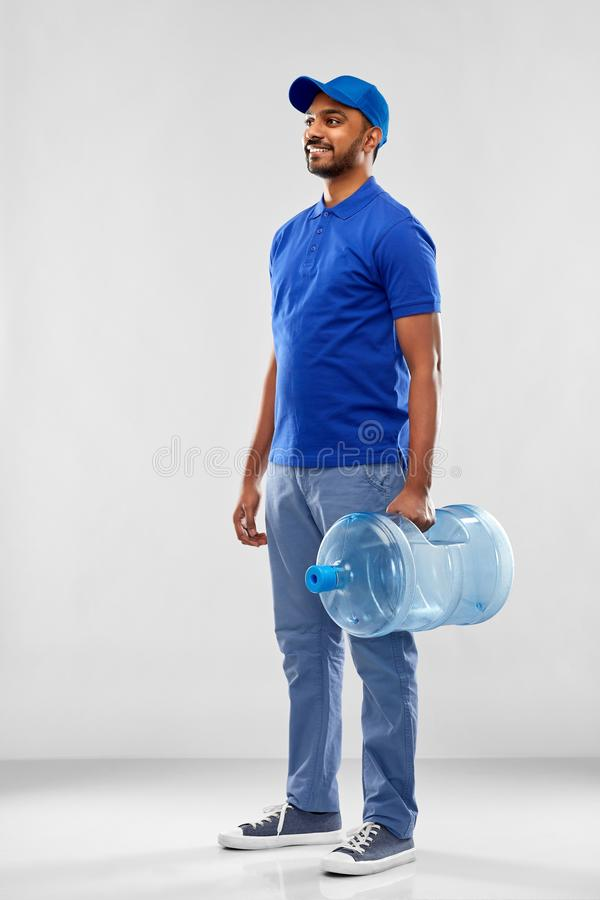 Happy indian delivery man with water barrel. Service and people concept - happy indian delivery man with water barrel in blue uniform over grey background royalty free stock images