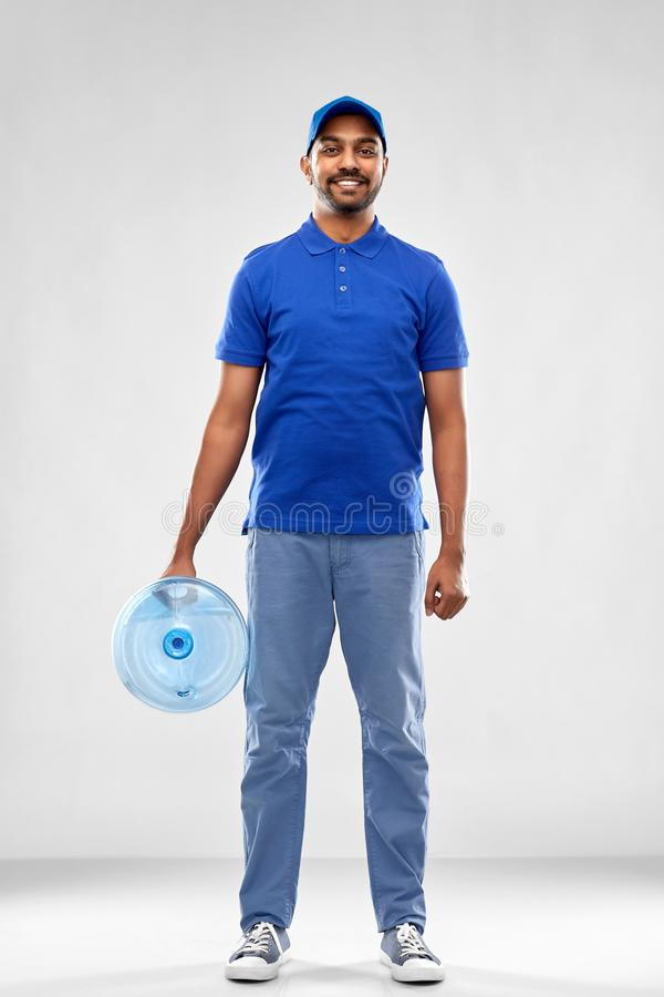 Happy indian delivery man with water barrel. Service and people concept - happy indian delivery man with water barrel in blue uniform over grey background royalty free stock photography