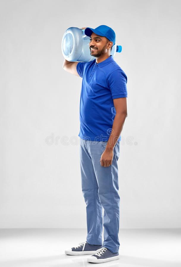 Happy indian delivery man with water barrel. Service and people concept - happy indian delivery man with water barrel in blue uniform over grey background royalty free stock photos