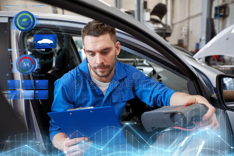 Mechanic man with diagnostic scanner at car shop. Service, repair, maintenance and people concept - mechanic man with automotive diagnostic scanner and clipboard stock photography