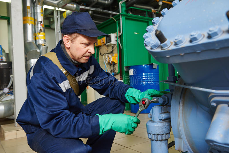 Service worker at industrial compressor station. Service engineer worker at industrial compressor refrigeration station repairing and adjusting equipment at stock images