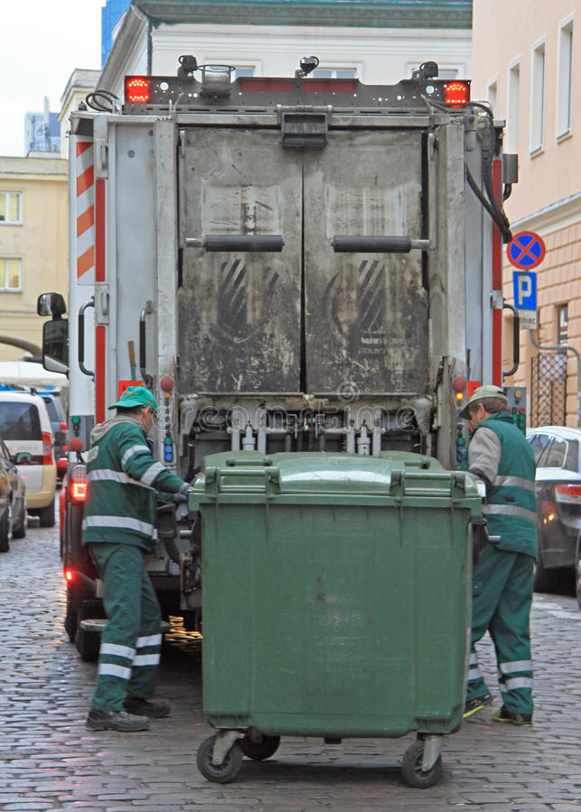Service workers is loading trash from dustbin to garbage truck. Warsaw, Poland - October 23, 2015:service workers is loading trash from dustbin to garbage truck royalty free stock photography