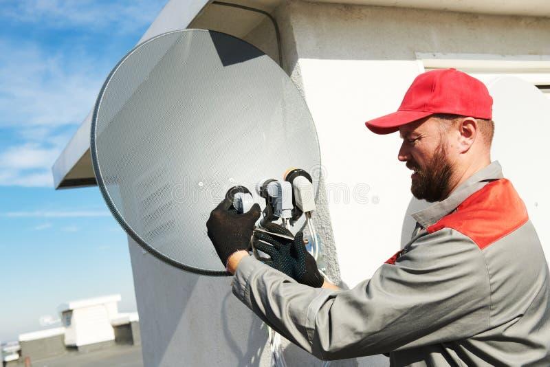Servicearbetare som installerar och passar maträtten för satellit- antenn för kabel-TV royaltyfri fotografi