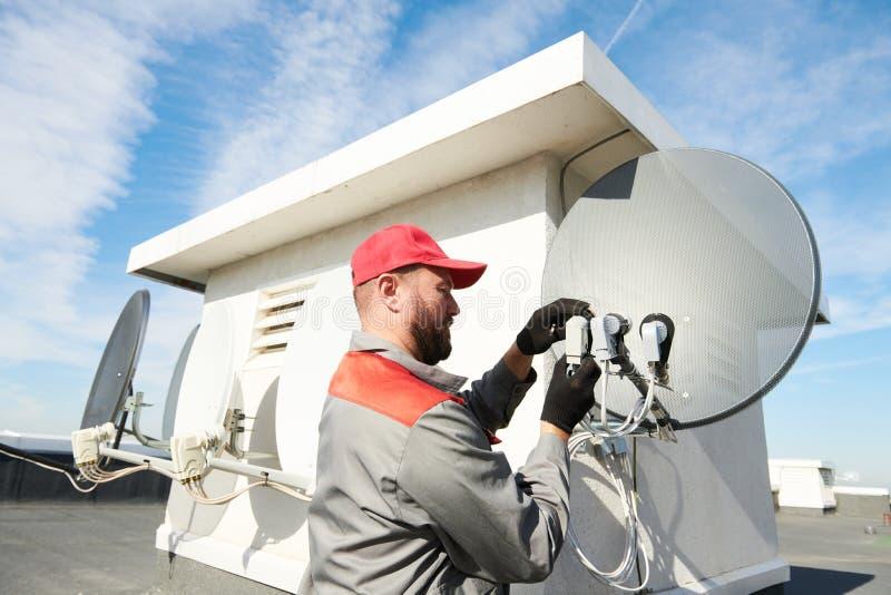 Servicearbetare som installerar och passar maträtten för satellit- antenn för kabel-TV royaltyfri foto