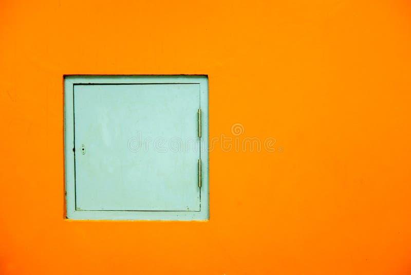Servicedörrar av byggnaden, väggar målade orange färg arkivbild